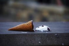 Ice cream cone on a stone bench, next to fallen ice cream scoop