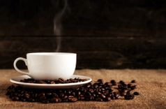 Cup of steaming coffee, sitting on a saucer that is filled with and surrounded by coffee beans, all on top of a tablecloth of burlap