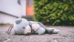 Torn teddy bear on the sidewalk